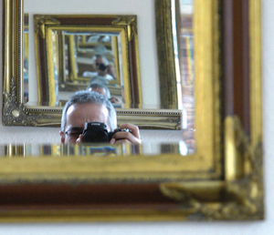 A man behind a camera, taking a photo of himself in a mirror, with multiple reflections