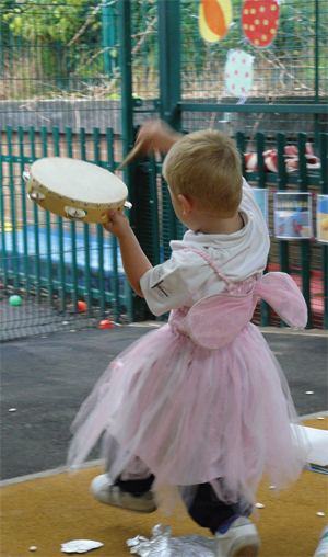 Boy plays a tambourine as he runs around in a fairy costume