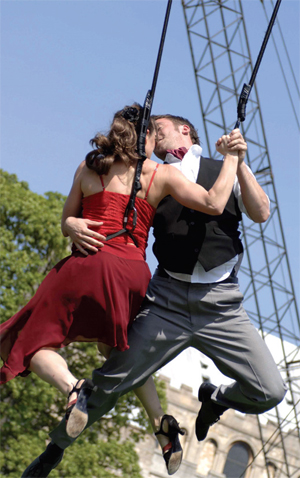 A couple in harnesses in the air, embrace, as part of a performance piece