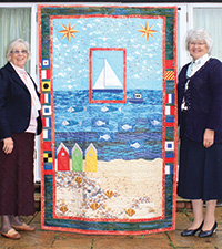 Two older ladies stand by a large quilt (with a seafront design, including beach, sea and beach huts).