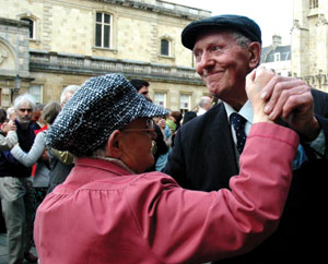An elderly couple dance amongst a crowd of waltzing couples