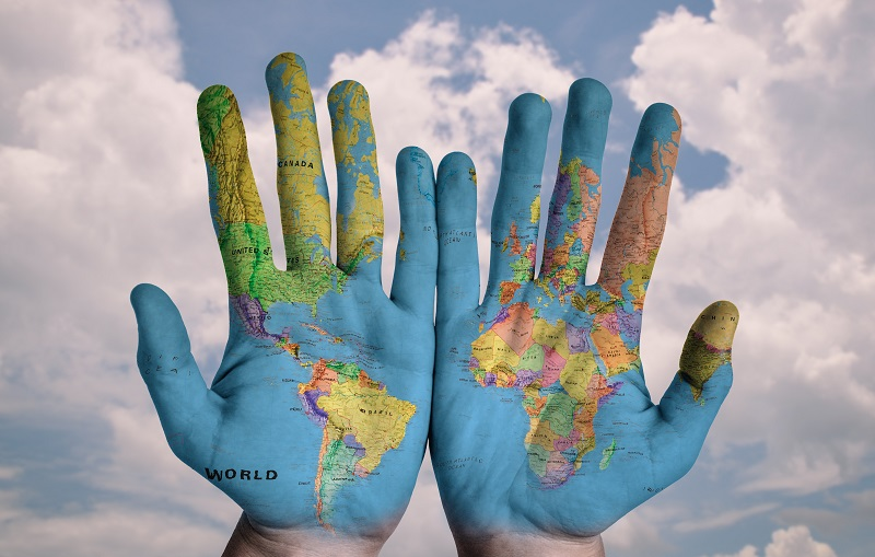 Photo of hands with world map on them