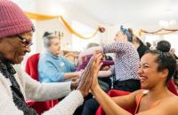 Photo of older woman and dancer clapping hands together
