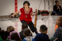 Woman with violin teaching young children in a school hall
