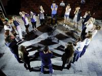 A group of young people stand in a cirle with their hands to their faces in an acting exercise.