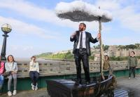 Performance shot: man in boat under a raining umbrella