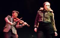 Photo of performance of violinist and woman in masks