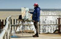 Photo of a man painting by the sea