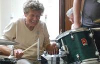 An older woman playing a drum kit
