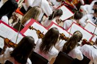 children playing violins in an orchestra