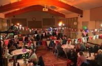 A photo of a village hall with tables of people sitting down