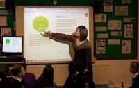 Photo of teacher pointing at screen