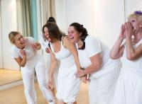 Photo of women wearing white acting in studio