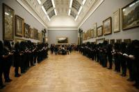 People dressed in black stand in large gallery