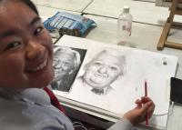 Girl doing a pencil sketch from a model