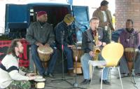 a group of men in a band playing instruments outside a van