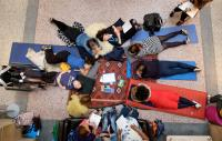 A group of diverse people gathered in a circle on the floor