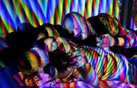A group of people lit by multi-coloured light