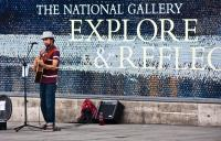 Photo of busker by National Gallery sign