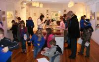 A photo of children in a gallery with pictures on the wall