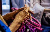 A close up photo of a persons' hands resting on a pink handbag
