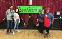 Four people standing on stage in front of a sign saying 'Save Granville'