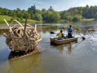Photo of people in rowing boat towing a wooden sculpture