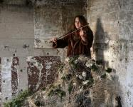 Photo of woman playing violin in concrete room