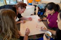 Group of women drawing stickmen around a table
