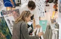 two women flicking through painting canvasses in a studio or shop setting