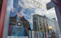 Reflections of a street scene in a coffee shop window
