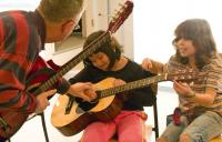 A photo of two children playing guitar next to an adult holding a guitar