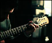 Photo of a man playing a guitar