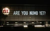 """Projection of """"Are you numb yet?"""" onto a building"""