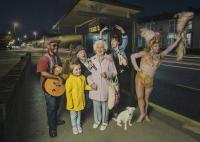 Photo of performers and family at a bus stop
