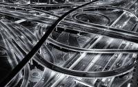 mono photograph showing an aerial view of a road network taken at night with cars visible on the carriageways