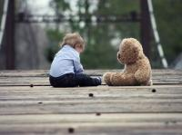 Boy and teddy bear on bridge