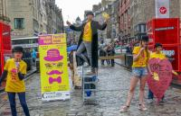 People standing next to a street billboard at the Edinburgh Fringe Festival