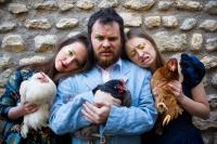 Photo of three people holding chickens