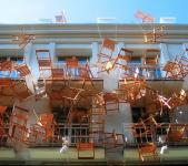 Photo of chairs hanging in front of building