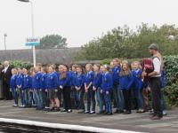 Image of children singing on railway platform