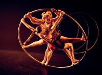 Photo of three circus performers in large hoop