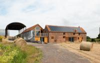 Clayhill Arts building. A converted barn in a rural landscape with hay bales in the foreground