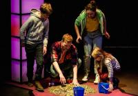 Actors collecting coins off the floor during a production