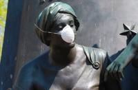 Statue of a woman with a mask covering nose and mouth