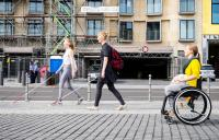 Photo of woman in wheelchair and two people with sticks