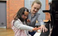 Photo of two children at piano
