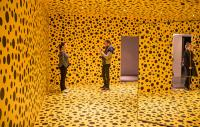 three people standing in an all-yellow room with black spots painted on the walls, ceiling and floor