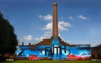 A building with a tall tower and a wall covered in a bright mural saying 'faith'