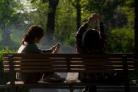 Photo of people on phones on a bench